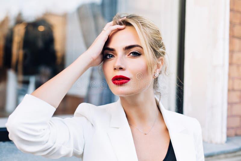Mujer atractiva del retrato del primer con los labios rojos en la calle Ella lleva la chaqueta blanca, tocando el pelo, mirando a fotos de archivo libres de regalías