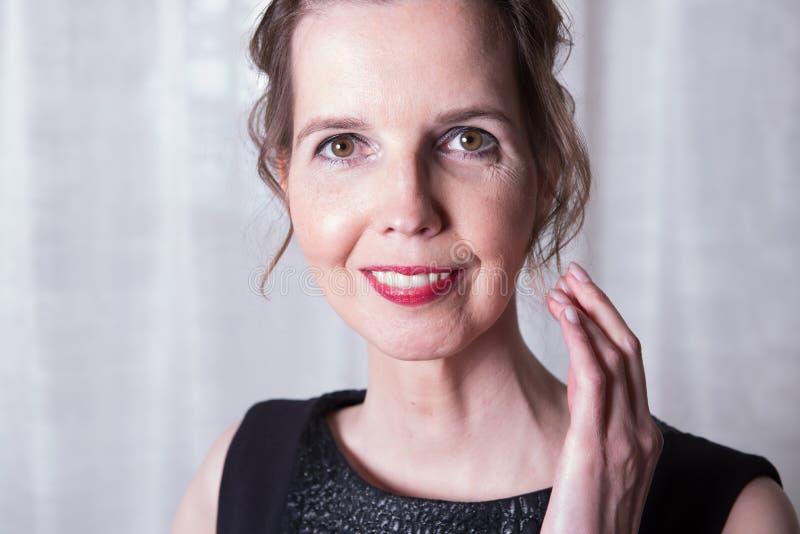 Mujer atractiva del retrato que está sonriendo imagen de archivo