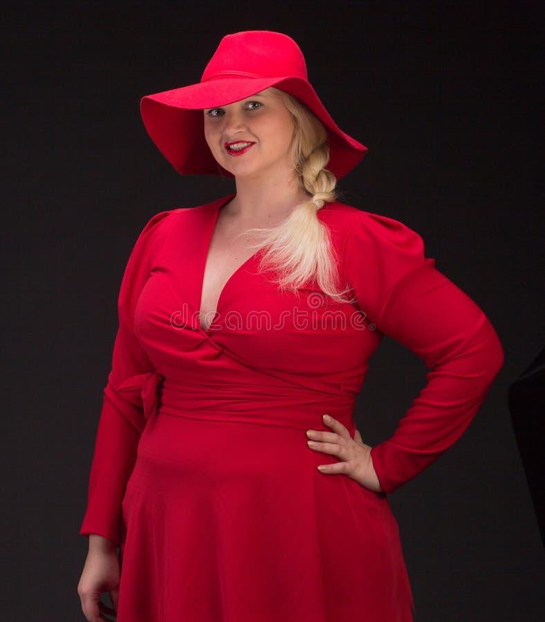Mujer atractiva del tamaño extra grande en sombrero rojo con los labios rojos fotos de archivo libres de regalías