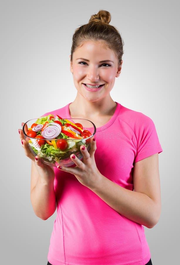 Mujer atractiva delgada con la ensalada vegetal fotografía de archivo libre de regalías