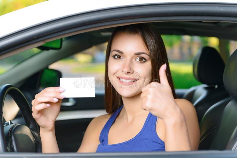 Mujer atractiva dentro del coche que muestra la tarjeta imagen de archivo
