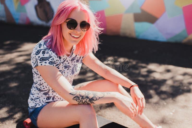 Mujer atractiva deportiva con el pelo rosado y la sonrisa sana, con el tatuaje a mano, sentándose en su esperar del longoard fotos de archivo libres de regalías