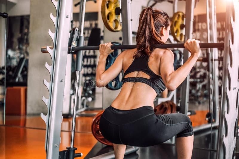 Mujer atractiva deportiva hermosa que hace entrenamiento agazapado en club de deporte del centro de formación del entrenamiento d fotos de archivo