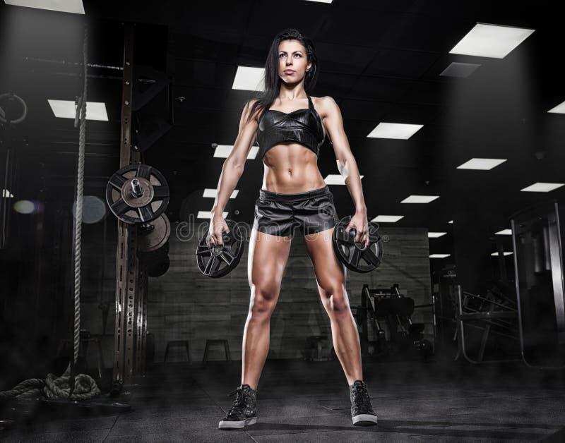 Mujer atractiva deportiva hermosa que hace entrenamiento agazapado en gimnasio fotografía de archivo libre de regalías
