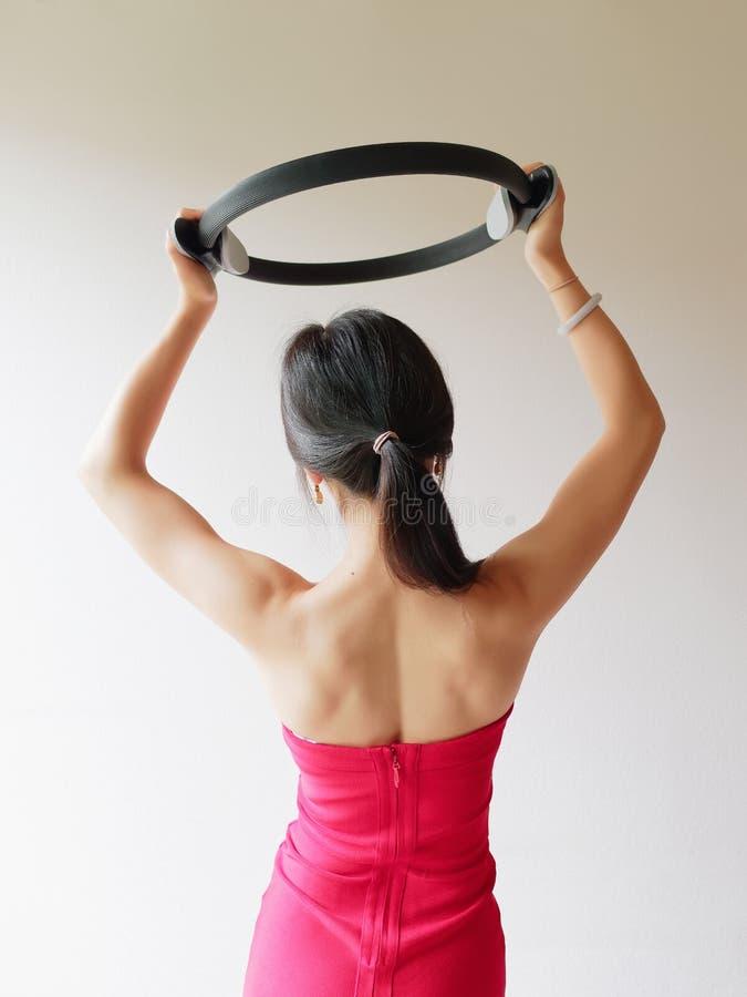 Mujer atractiva deportiva joven que hace los pilates que entonan el ejercicio para los brazos y los hombros con el anillo, aptitu foto de archivo