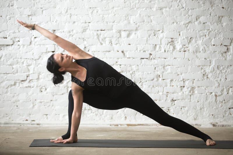 Mujer atractiva en actitud del parsvakonasana de Utthita, desván de la yogui joven imagen de archivo libre de regalías
