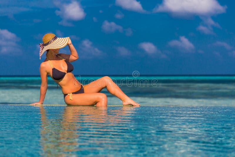 Mujer atractiva en bikini en la piscina, mirando el fondo del mar en Maldivas foto de archivo