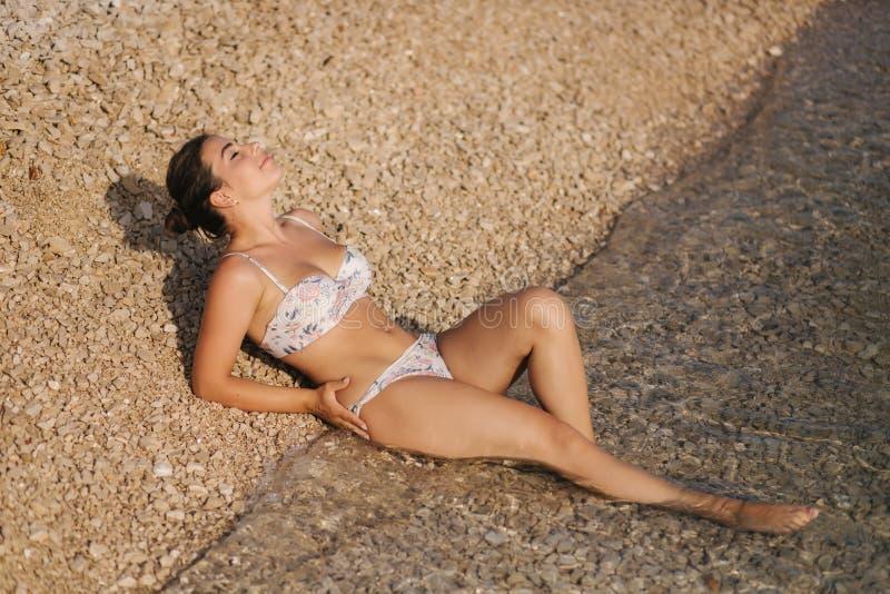 Mujer atractiva en bikini en la playa que goza del sol del verano La mujer hermosa miente cerca del mar El agua moja sus pies fotografía de archivo