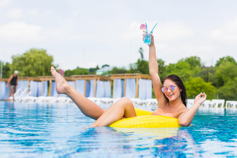 Mujer atractiva en bikini que goza del sol del verano y que broncea durante días de fiesta en piscina con el cóctel Visión superi imagen de archivo libre de regalías