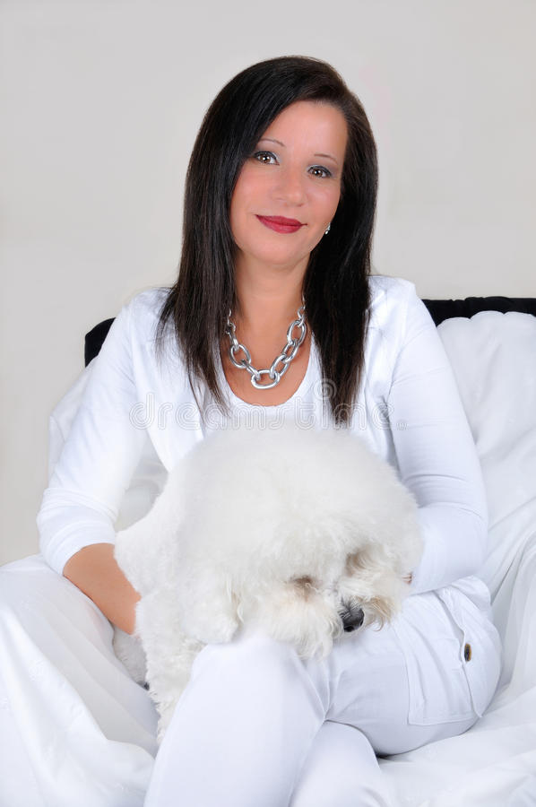 Mujer atractiva en blanco con el perro mullido blanco fotos de archivo