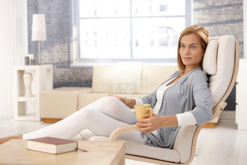 Mujer atractiva en butaca con la taza de café imagen de archivo