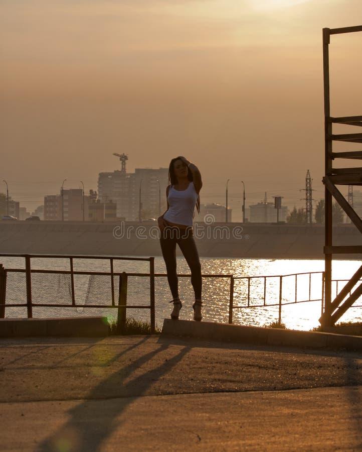 Mujer atractiva en ciudad en la puesta del sol imagenes de archivo