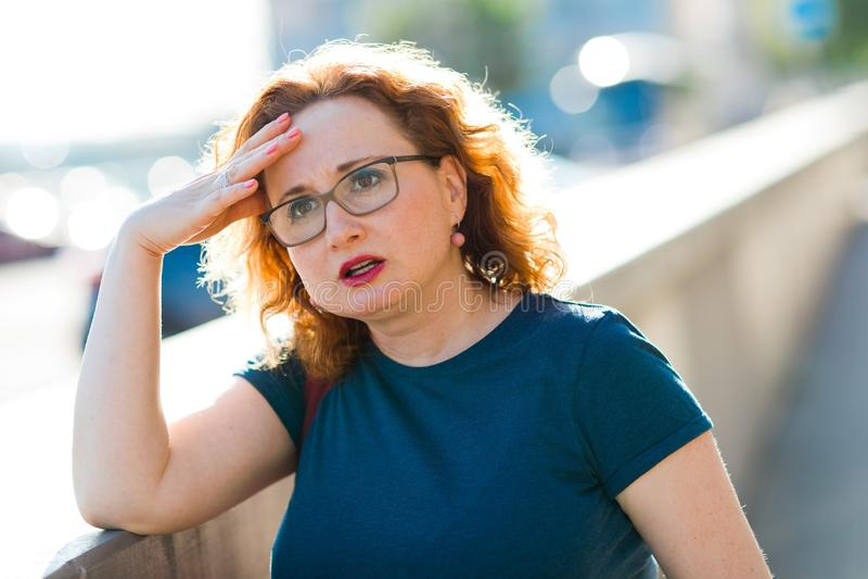 Mujer atractiva en el dolor principal súbito de la sensación de la calle imagen de archivo libre de regalías