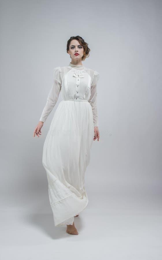 Mujer atractiva en el vestido retro largo blanco imagen de archivo