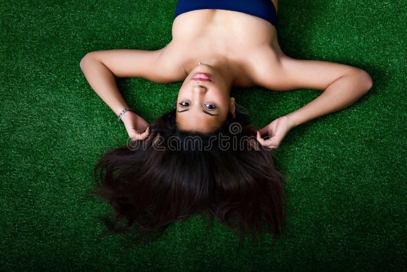 Mujer atractiva en hierba foto de archivo