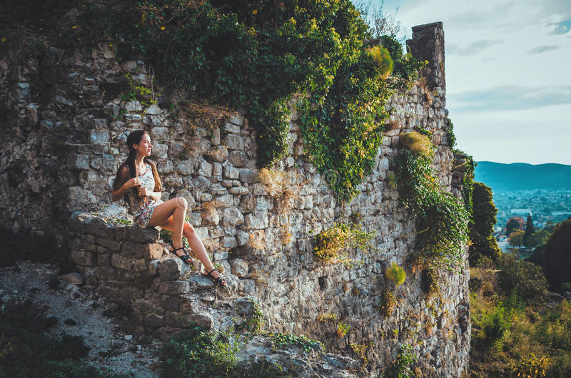 Mujer atractiva en la fortaleza vieja de la barra de Stari, Montenegro La hembra morena con el pelo largo en vestido camina alred foto de archivo libre de regalías