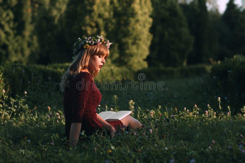 Mujer atractiva en la lectura de la guirnalda en naturaleza imagen de archivo libre de regalías