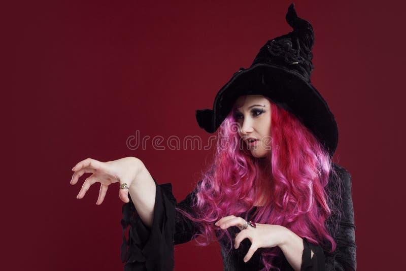 Mujer atractiva en las brujas sombrero y traje con el pelo rojo Víspera de Todos los Santos foto de archivo
