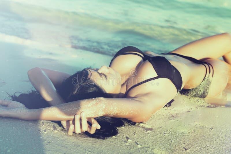 Mujer atractiva en las vacaciones de la playa que mienten en la arena imagen de archivo