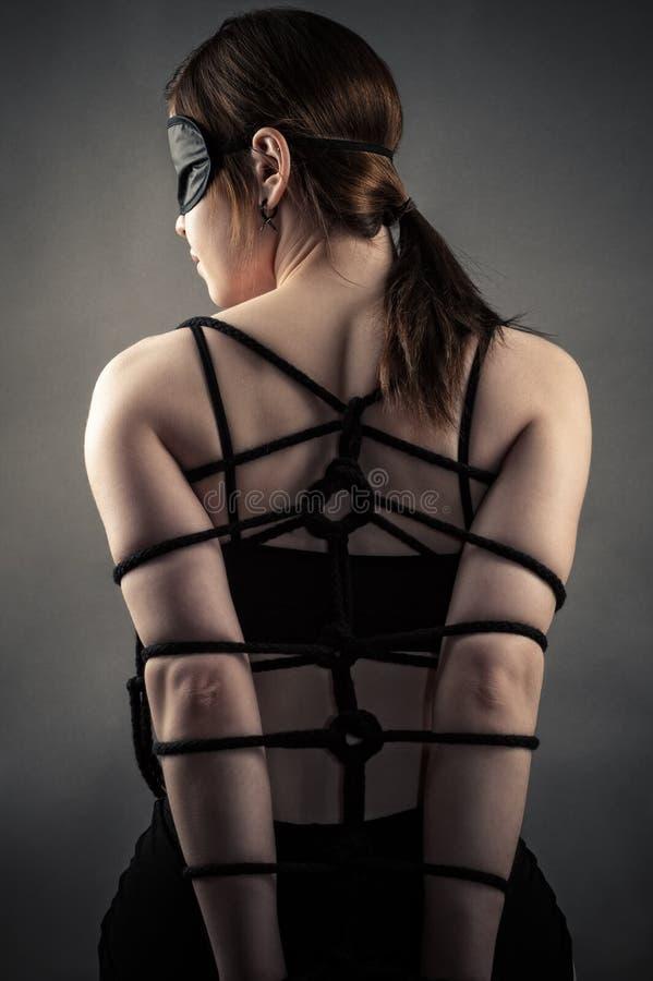Mujer atractiva en manos de la máscara y de la esclavitud imagen de archivo