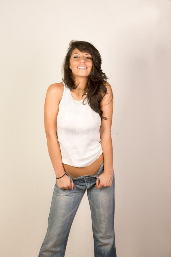 Mujer atractiva en pantalones vaqueros y tanque-tapa fotos de archivo