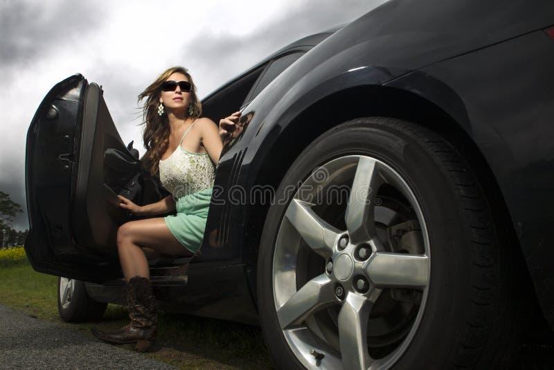 Mujer atractiva en salir de las botas del coche foto de archivo libre de regalías