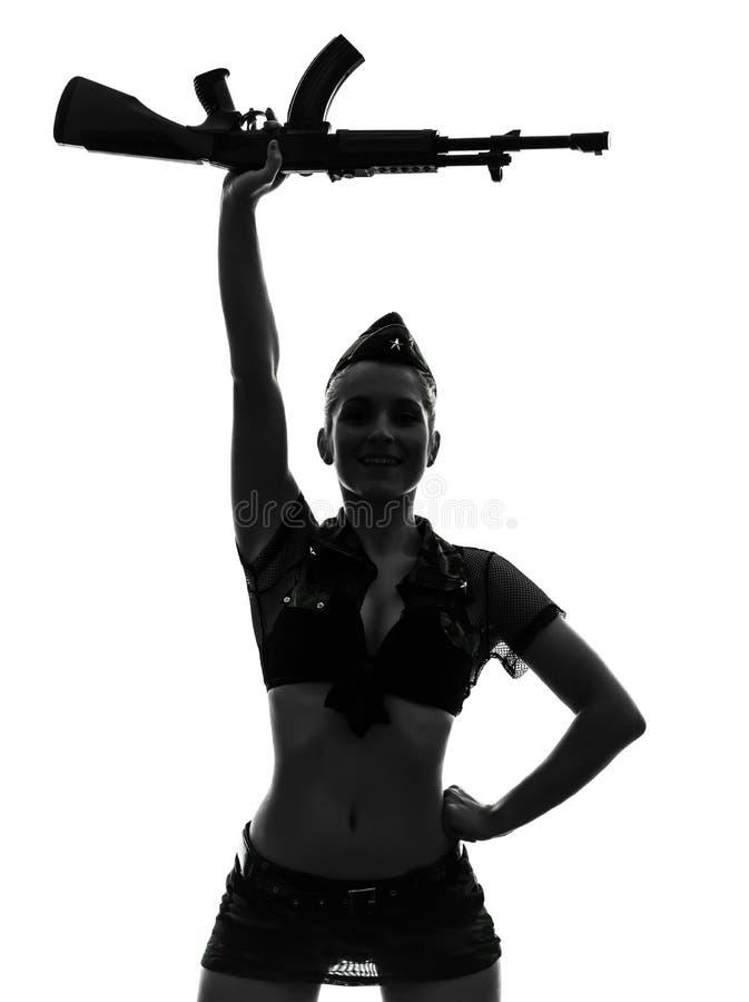 Mujer atractiva en silueta uniforme del kalachnikov del ejército que saluda imagen de archivo libre de regalías