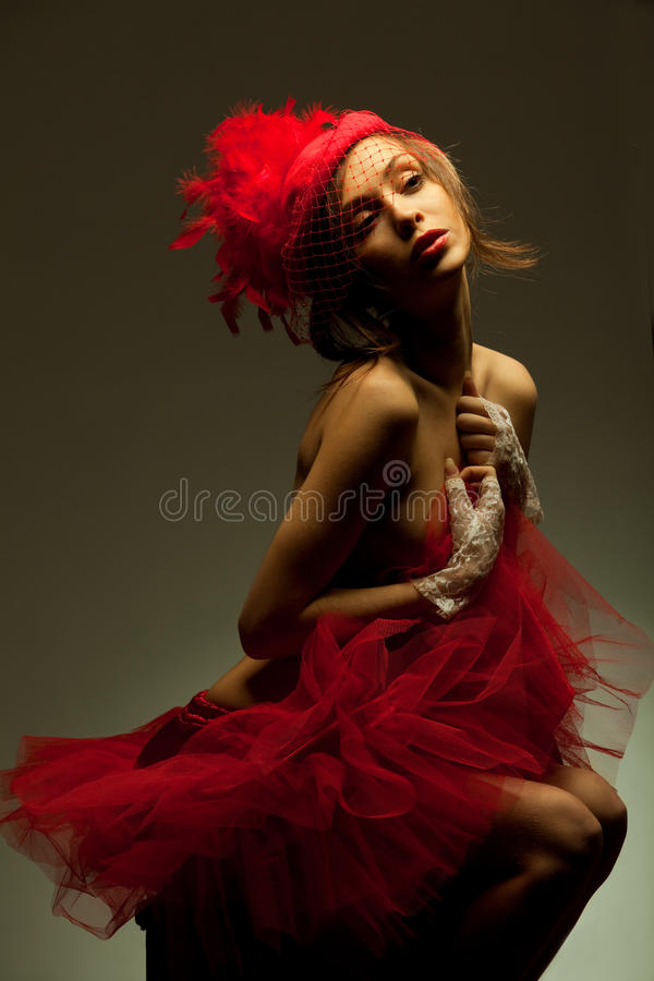 Mujer atractiva en sombrero rojo con el velo neto imagen de archivo