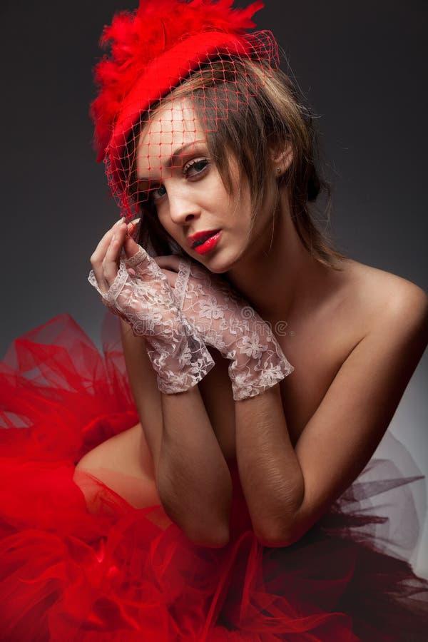 Mujer atractiva en sombrero rojo con el velo neto fotografía de archivo
