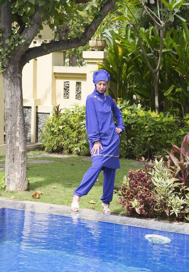 Mujer atractiva en soporte musulmán del burkini del traje de baño en un lado de la piscina en un jardín tropical imágenes de archivo libres de regalías