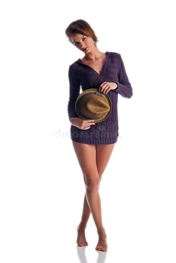 Mujer atractiva en un suéter púrpura que sostiene un sombrero foto de archivo libre de regalías