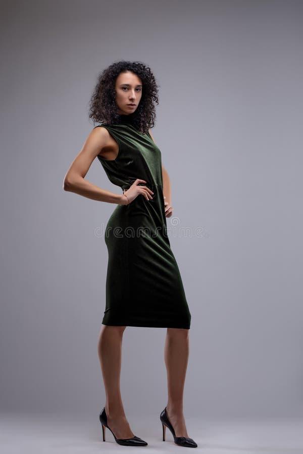 Mujer atractiva en un vestido negro elegante foto de archivo