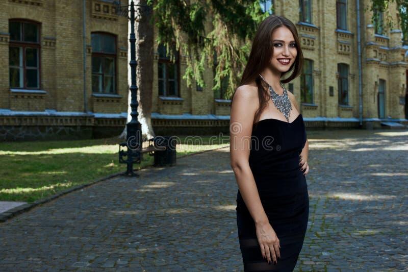 Mujer atractiva en vestido y collar negros fotos de archivo libres de regalías