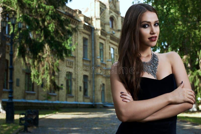 Mujer atractiva en vestido y collar negros foto de archivo