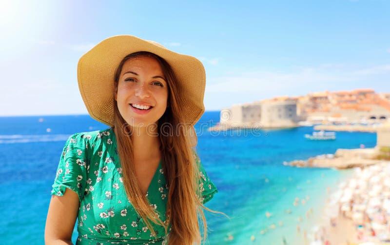 Mujer atractiva feliz del viajero en Croacia con la ciudad y el mar Mediterráneo viejos en el fondo, Europa de Dubrovnik foto de archivo