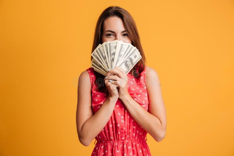 Mujer atractiva feliz joven en el vestido rojo que oculta detrás de manojo de foto de archivo libre de regalías