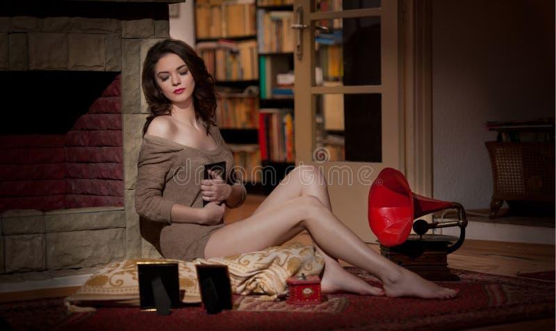 Mujer atractiva hermosa cerca de un gramófono rojo rodeado por los marcos de la foto en paisaje del vintage. Retrato de la muchach imagen de archivo