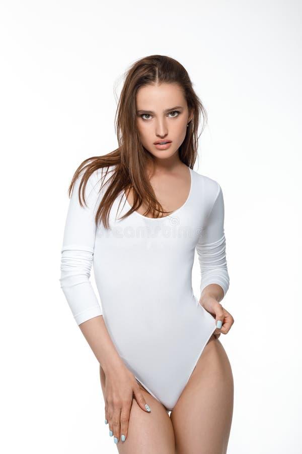 Mujer atractiva hermosa con el cuerpo perfecto en el mono blanco imagenes de archivo