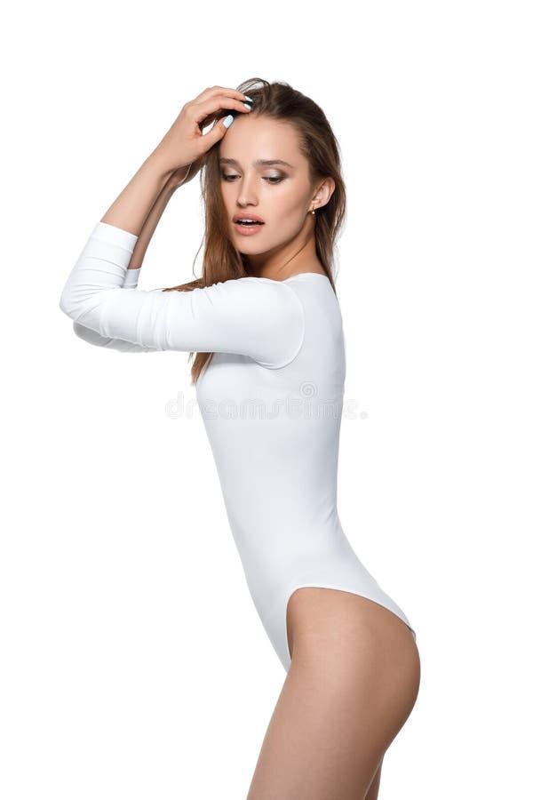 Mujer atractiva hermosa con el cuerpo perfecto en el mono blanco foto de archivo libre de regalías