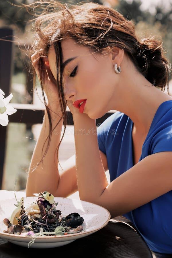 Mujer atractiva hermosa con el pelo oscuro en la ropa elegante que sienta i fotos de archivo