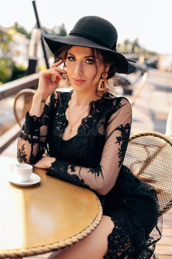 Mujer atractiva hermosa con el pelo oscuro en vestido y sombrero negros elegantes imagen de archivo libre de regalías