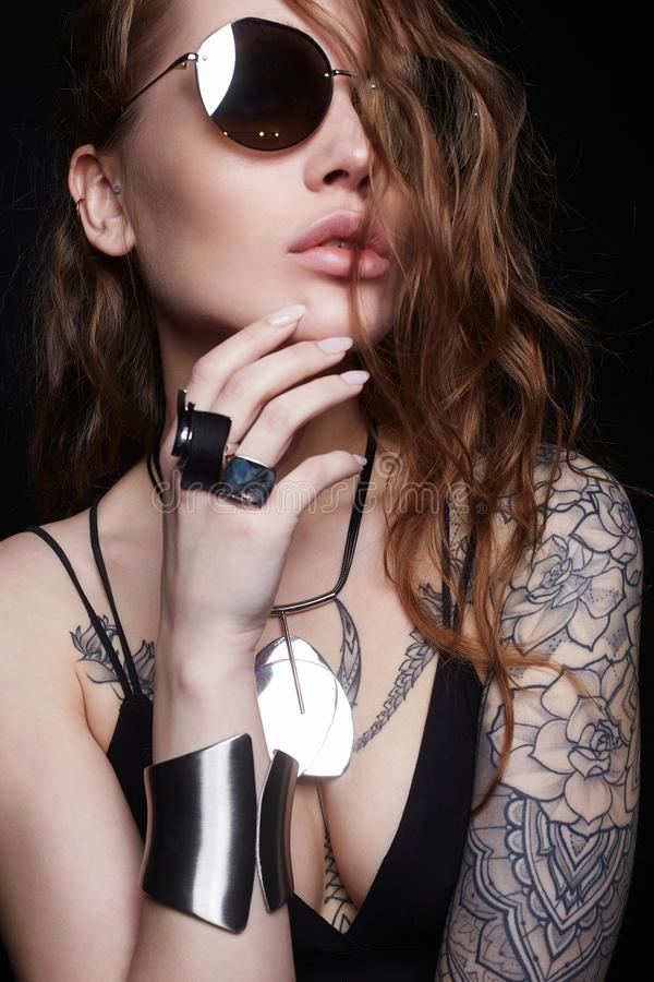 Mujer atractiva hermosa con el tatuaje Muchacha en gafas de sol fotografía de archivo libre de regalías