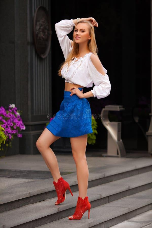 Mujer atractiva hermosa con la presentación de la falda azul y del pelo rubio al aire libre Muchacha de la manera imagen de archivo