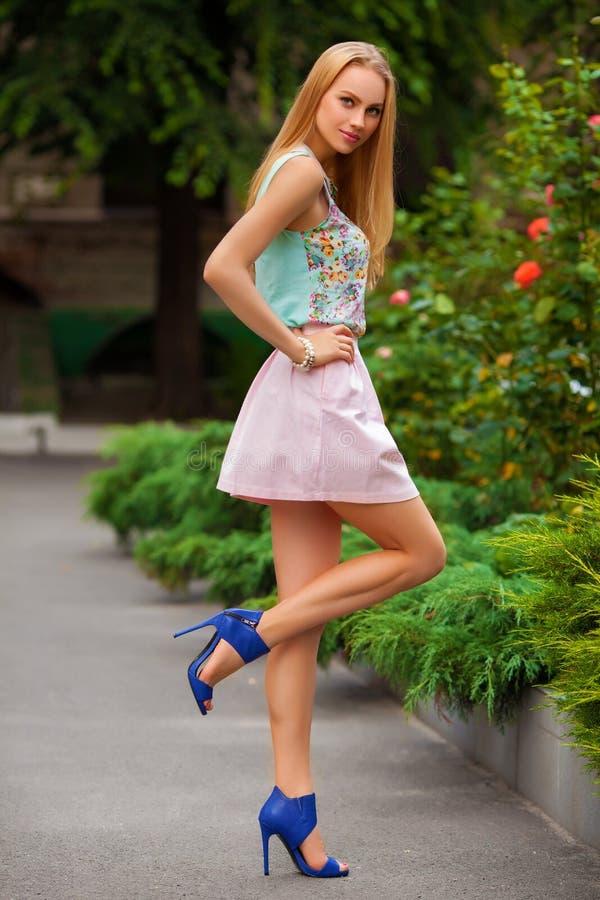 Mujer atractiva hermosa con la presentación de la falda rosada y del pelo rubio al aire libre Muchacha de la manera fotos de archivo
