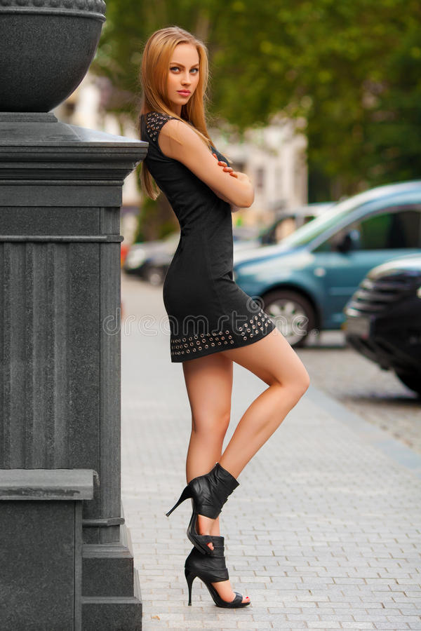 Mujer atractiva hermosa con la presentación del vestido negro y del pelo rubio al aire libre Muchacha de la manera fotografía de archivo