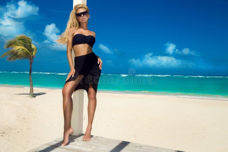 Mujer atractiva hermosa en el bikini que presenta en la playa del Caribe fotos de archivo libres de regalías