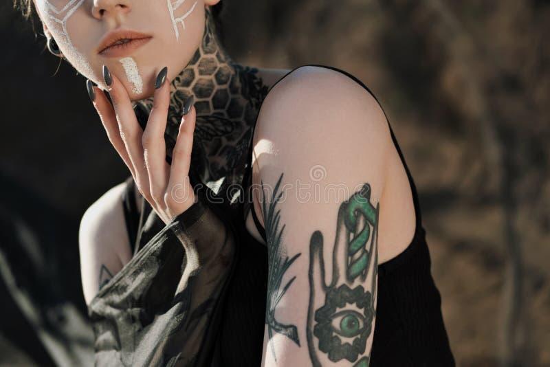 Mujer atractiva hermosa en ropa interior negra El cuerpo se cubre con muchos tatuajes Dreadlocks en la cabeza Presentaci?n contra imágenes de archivo libres de regalías