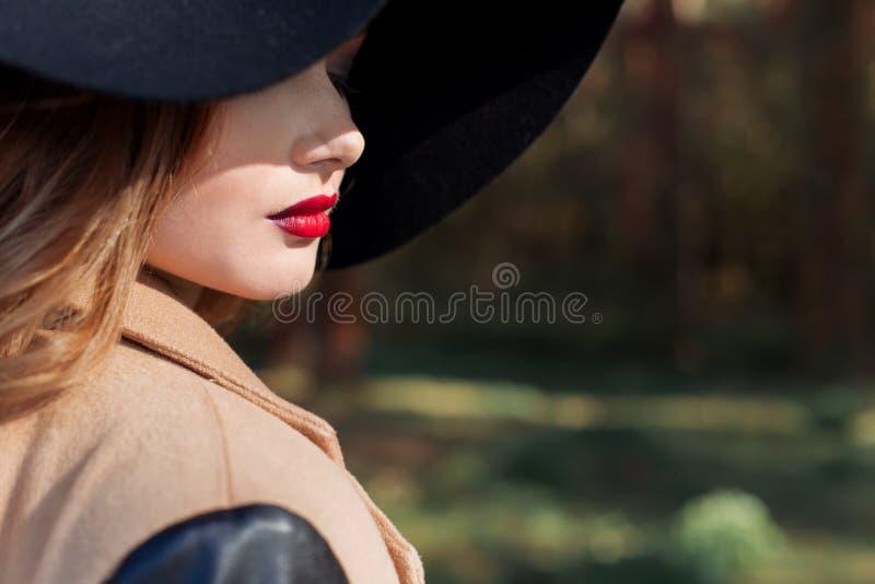 Mujer atractiva hermosa en sombrero negro elegante con los campos grandes y lápiz labial rojo brillante en sus labios fotografía de archivo