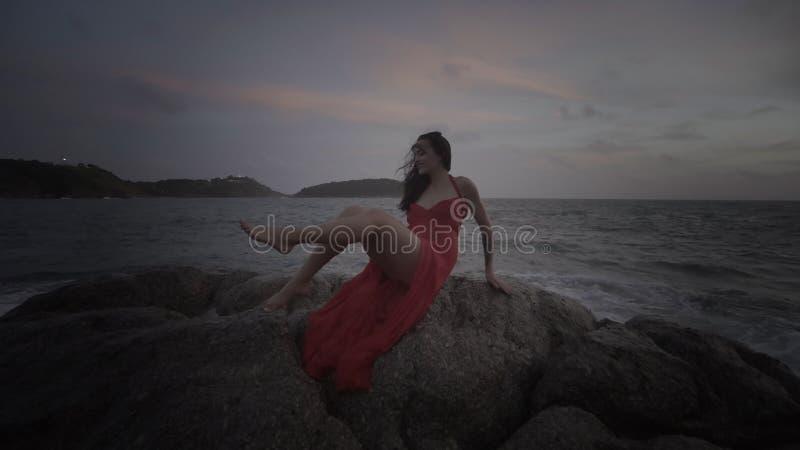 Mujer atractiva hermosa en vestido rojo que se goza en rocas por el mar fotografía de archivo libre de regalías