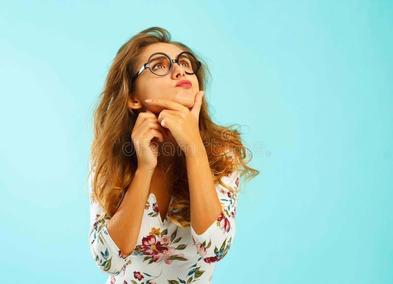 Mujer atractiva hermosa en vidrios redondos sobre fondo azul imágenes de archivo libres de regalías